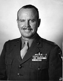 Head & torso of white man with slightly receding hairline and waxed mustache wearing tan shirt and necktie, green blouse with U.S. Marine Lieutenant Colonel's insignia, five rows of ribbons on his chest, and 2nd Marine Division patch on his left shoulder. The U.S. Marine Corps logo is superimposed on the lower right corner of this black & white photograph.