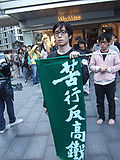 person wearing spectacles carrying a green banner with the words '苦行反高鐵' (penance against High-speed rail link) leading a group of protesters