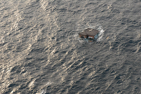 A Japanese home is seen adrift in the Pacific Ocean. Image: U.S. Navy.