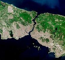 Image satellite montrant un mince morceau de terre, densément peuplé au sud, coupé en deux par une voie navigable