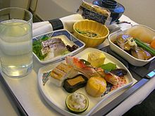 A picture with a glass of water on the left, a napkin on the top, with two bowls on the far right and three dishes in the center and right, all contained on a serving tray