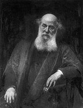 An elderly man wearing dark robes, sitting in a chair with his left arm on the armrest; the top of his head is bald and he has a long white beard