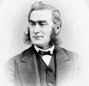 1870s in Western fashion - Canadian legislator John Charles Rykert wears a narrow ribbon necktie and a collarless waistcoat. His coat has wide lapels. 1873.