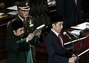 Inauguration of Joko Widodo - Joko Widodo reciting his presidential oath under a copy of the Quran.