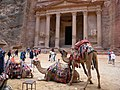 Jordan, Petra (El Deir). Tourists and camels in front of Monument Pharaaoh's Treasury.jpg