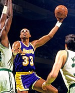 "A man, wearing a purple jersey with the word ""LAKERS"" and the number 33 on the front, is trying to shoot the basketball while being guarded by two man who are wearing white jerseys."