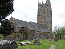 Gray stone building with ornate square tower and slate roof. In the foreground are gravestones