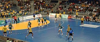Handball - The referees (blue shirts) keep both teams between them.