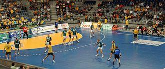 Handball - The referees (blue shirts) keep both teams between them.