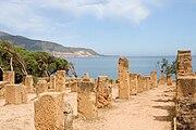 gränd kantad med förstörda rektangulära pelare, med havet i bakgrunden