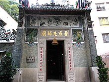 The exterior of a temple, with a large door flanked by Chinese characters. Other urban buildings can be seen in the background.
