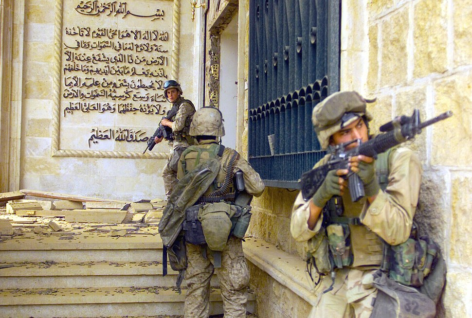 Color photograph of three U.S. Marines entering a partially destroyed palace