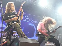 "A color photograph of two members of the group Blazers of Gilstar standing on a stage with guitars, drums are visible in the background. Both electric guitarists have ""flying V"" style guitars and they have long hair."