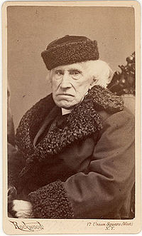 Photograph of seated, white-haired man in fur-trimmed coat and hat