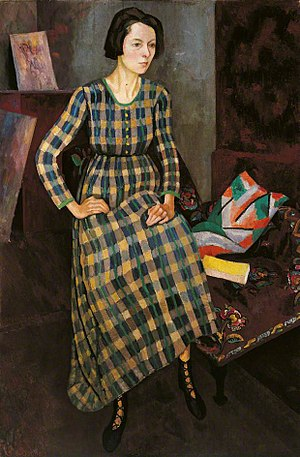 Omega Workshops - Nina Hamnett painted by Roger Fry, 1917, in a dress designed by Vanessa Bell and made at the Omega. The shoes may also be from Omega and the cushion on the chair is covered with 'Maud' linen, also by Bell.