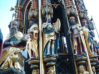 Nine Worthies - Statues of the Nine Worthies on the Schöne Brunnen (beautiful fountain) in Nuremberg (1385-1396). Visible on the fountain, l to r are: Judas Maccabeus, David (with harp), Julius Caesar, Alexander. The figure in the left foreground, St Mark, with his lion, is part of another group