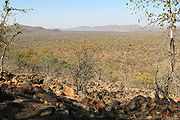 A broad expanse of dry savanna with hills in the background. The foreground contains large rocks on the ground with two trees flanking the sides of the picture.