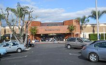 "A view of a single-story brown brick building from a parking lot in front, with palm trees on either side of the frame. In the center is a red brick entrance pavilion with ""Panorama Mall"" written on it in stylized metal letters"
