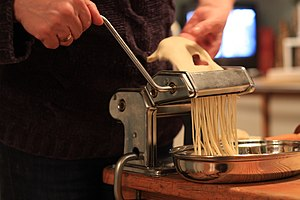 Spaghetti - Fresh spaghetti being prepared using a pasta machine
