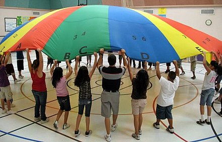 Kids using a parachute during a PE lesson Pe class.jpg