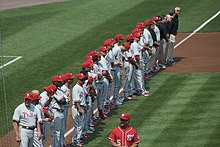 A row of men wearing gray baseball uniforms with red trim and red baseball helmets standing in a line down a dirt path on a grass field