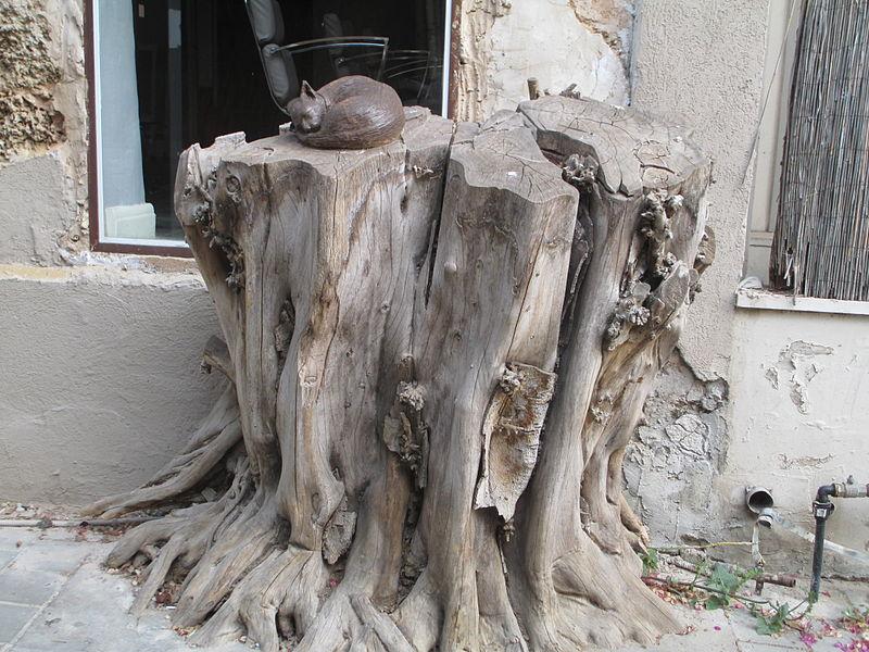 פסל חתול ישן על גדם עץ