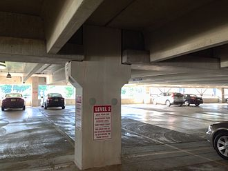 Precast concrete - Precast parking structure showing an interior column, girders, and double-tee structural floors. The two gray circles are covers to close the lifting anchor holes.
