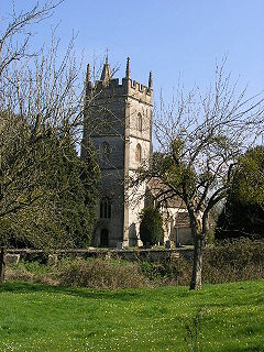 Stone building with prominent square tower. Surrounded by trees and with green grass area in the foreground separated from the building by a stone wall.