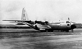 Four-engined military transport plane parked on airfield