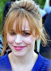 An image of a Caucasian women wearing a blue top. She is smiling and has her light brown hair tied back with bangs. Her natural darker brown hair color is showing by the roots.
