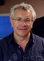 A white haired man is seen wearing a blue collared shirt.