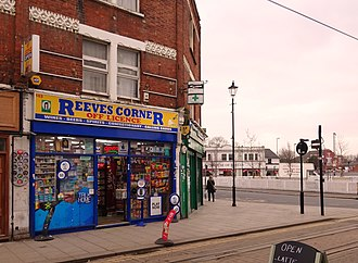 House of Reeves - Reeves Corner Off Licence. The House of Reeves is visible in the background; while the plot behind the picket fence is the site of the buildings destroyed in 2011.