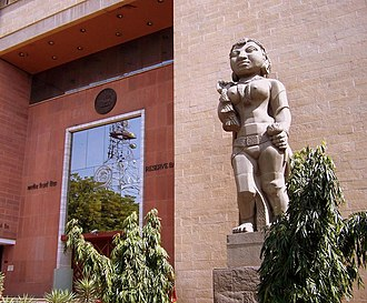"""Yakshini - Reserve Bank of India headquarters, Delhi entrance with a Yakshini sculpture(c. 1960) depicting """"Prosperity through agriculture""""."""