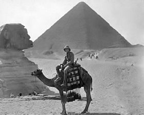 Man in military uniform and pith helmet sitting on a camel in front of the Sphinx and Pyramid