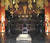 Elaborately decorated room, symmetrical, with a gold colored statue on an altar