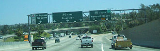"""California State Route 91 - Eastbound SR 91 at SR 55 (right) and 91 Express Lanes (left). The """"button style"""" sign on the left was replaced with a """"FASTRAK ONLY"""" sign in 2017."""