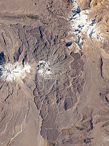 A volcano surrounded by expanding lava flows, left and right two snow covered summits, as seen from space