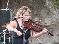 Watkins playing fiddle onstage