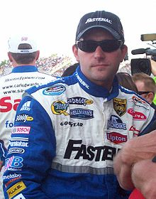 Scott Wimmer in his blue racing suit with a white chest filled with sponsors, wearing sunglasses and a black Fastenal baseball cap