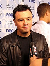 A man with black hair, wearing a leather jacket, and being interviewed. There is a small microphone in front of him, with a television channel logo placed on it.