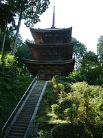 Wooden three-storied pagoda at the top of a long flight of stairs.