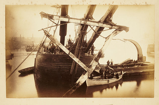 The photo, in sepia tones, shows a large ship on the River Tay bringing parts of the Tay Bridge to the surface