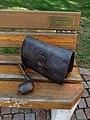 Sitzbank mit Pfeife und Herrenhandtasche vor dem Heimatmuseum Dornach.jpg