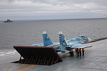 Rear port view of aqua-and-white jet aircraft lining up on aircraft carrier's deck, preparing for takeoff. The jet blast deflector is erected behind the aircraft. Three men in bright orange fluorescent tops stand underneath the jet's right wing