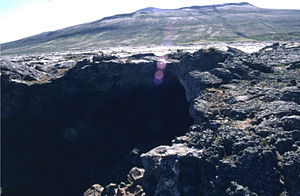 Surtshellir - The entrance to the Surtshellir lava tube at the Hallmundarhraun lava field, with Eiríksjökull in the background.