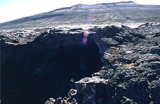 Surtshellir - The entrance to the Surtshellir lava tube at the Hallmundarhraun lava field, with Eiríksjökull in the background.