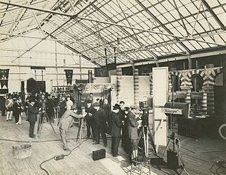 Thanhouser Company - Production still showing how three or more silent film scenes could be simultaneously filmed under the glass roof of the Thanhouser studio, c. 1914. Visible are actors in costume, directors, cameramen, sets, a Klieg light, and four Pathé silent film cameras