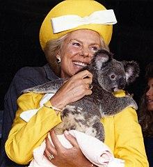 Une femme souriante dans des vêtements jaune vif tenant un koala