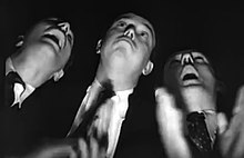 A photo from a low angle of three men looking ahead, clapping their hands and opening their mouths widely.