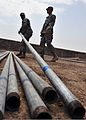 U.S. Army Sgt. Timothy Vandruff, left, and Spc. Steven Klinger, both with 2nd Battalion, 137th Infantry Regiment, Kansas National Guard, move fence posts at the police academy in Djibouti Sept 100901-N-AT895-018.jpg